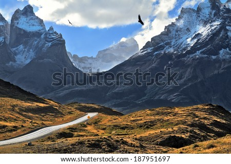 Grandiose landscape in the Chilean Andes. The road between turned yellow hills goes to snow-covered black rocks - stock photo