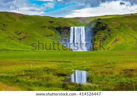 Grandiose reflection. The huge deep falls Skogafoss are reflected in small stream - stock photo