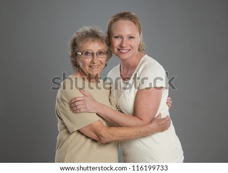 Grandma and Grand Daughter Hug Each Other on Grey Background - stock photo