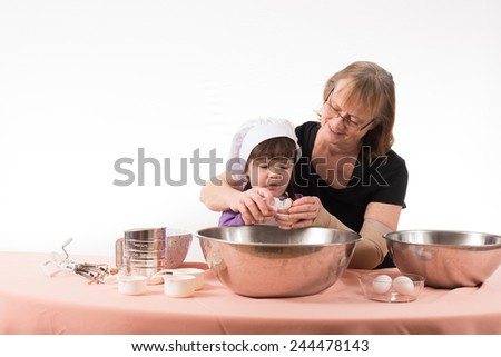 Grandma and granddaughter cracking an egg together - stock photo