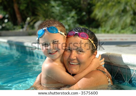 Grandma and her little treasure exercising the swimming pool with matching diving goggles - stock photo