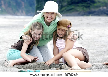 Grandma and her precious grandaughters at the beach - stock photo