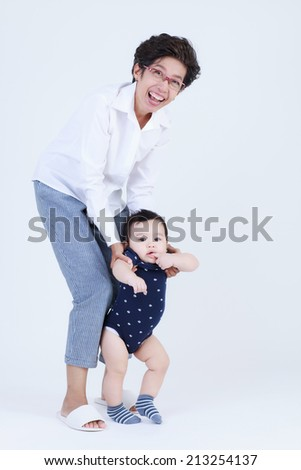 Grandma helping grandson to walk isolated - stock photo