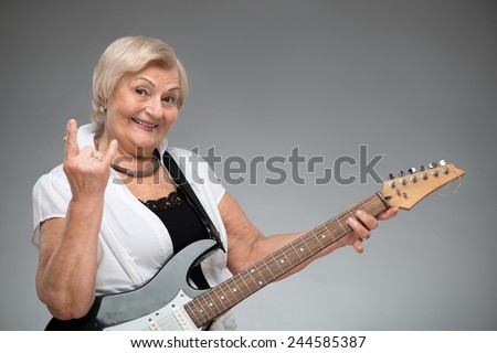 Grandma playing the guitar. Closeup of funny smiling senior woman playing the guitar and showing devils horns while standing against grey background - stock photo
