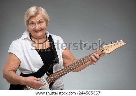 Grandma playing the guitar. Closeup of funny smiling senior woman playing the guitar while standing against grey background - stock photo