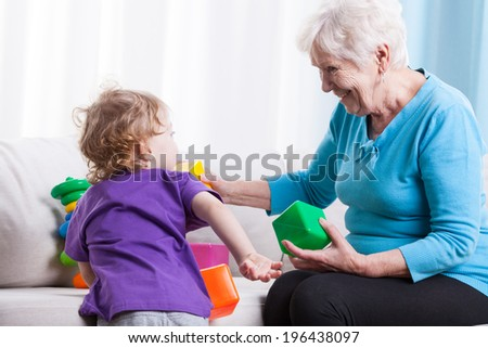Grandma playing with her grandchild on couch - stock photo