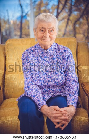 Grandma sitting in a yellow chair - stock photo