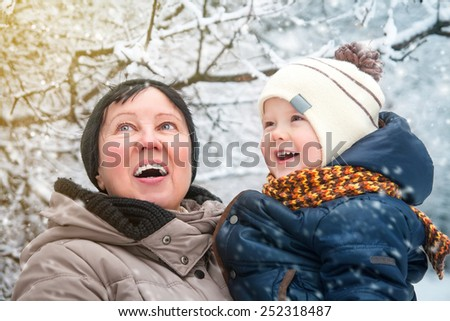 Grandmother and child in winter park - stock photo