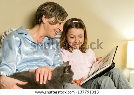 Grandmother and girl looking at photo album petting a cat - stock photo