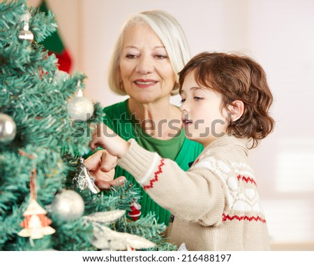 Grandmother and grandchild decorating christmas tree at home - stock photo