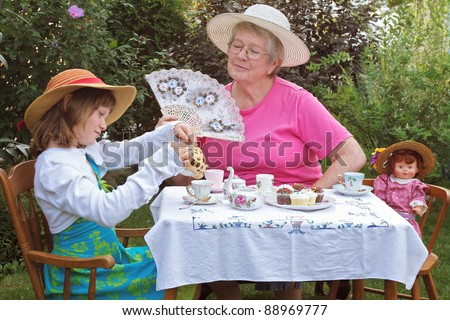 Grandmother and granddaughter enjoying a formal garden tea party - stock photo