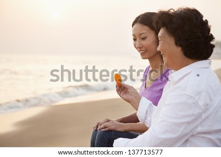 Grandmother and Granddaughter Looking At Seashell - stock photo