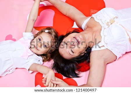 Grandmother and granddaughter lying on pink background - stock photo