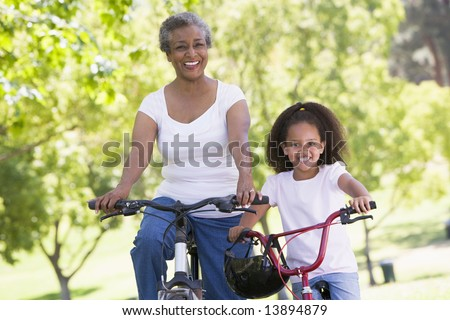 Grandmother and granddaughter on bikes outdoors smiling - stock photo