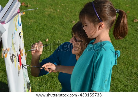 Grandmother and granddaughter paint together a colorful painting outdoor. - stock photo