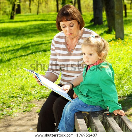 Grandmother and granddaughter reading a book outdoors - stock photo