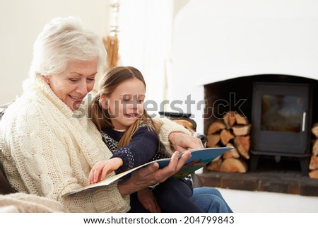 Grandmother And Granddaughter Reading Book At Home Together - stock photo