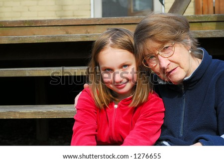 Grandmother and granddaughter sitting on a deck - stock photo