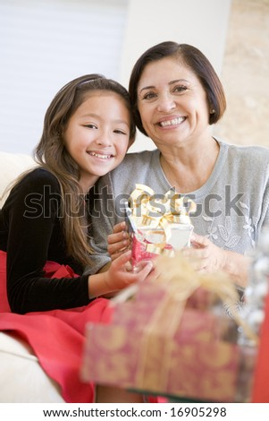 Grandmother And Granddaughter Sitting On Sofa Holding A Christmas Gift - stock photo