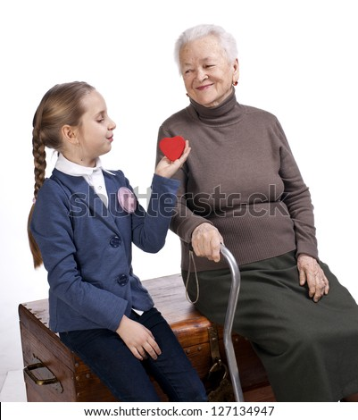 Grandmother and granddaughter with a  heart on a white background - stock photo