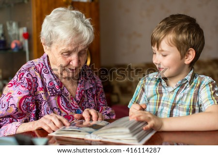 Grandmother and grandson looking photo album. - stock photo