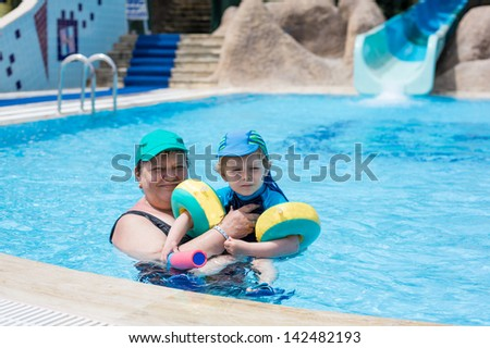 Grandmother and grandson swimming together in the pool. Outdoor, summer. - stock photo