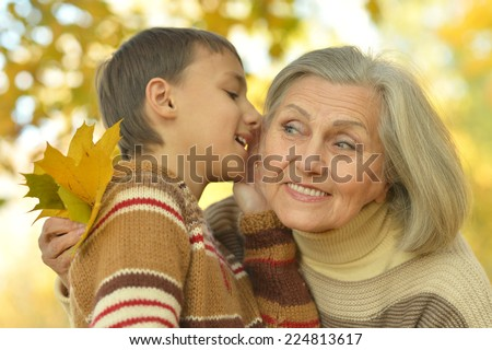 Grandmother and grandson walking in autumn park - stock photo