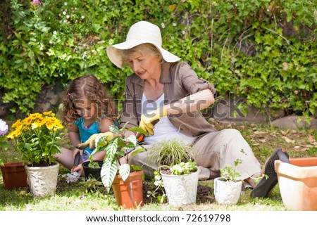 Grandmother and her granddaughter in the garden - stock photo