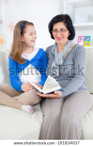 Grandmother and little girl reading a book happy together at home - stock photo