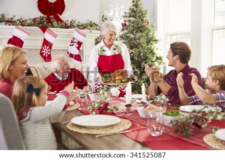 Grandmother Bringing Out Turkey At Family Christmas Meal - stock photo