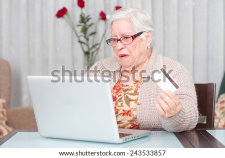 Grandmother buying online with credit card - stock photo