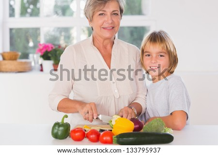 Grandmother cutting vegetables with her grandson in kitchen - stock photo