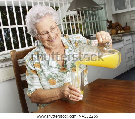 Grandmother drinking orange juice at kitchen. - stock photo