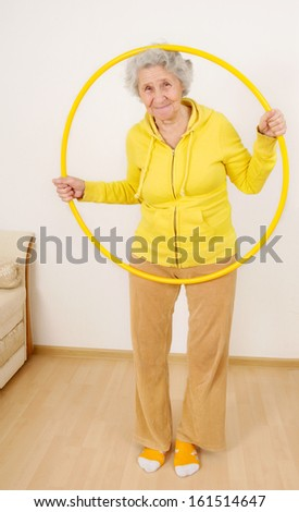 grandmother gymnastic exercises with hoop - stock photo