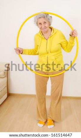 grandmother gymnastic exercises with hoop - stock photo