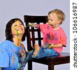 Grandmother is having fun letting her granddaughter paint her face. Both have paint all over their faces and clothes. Both seem to be enjoying themselves. - stock photo