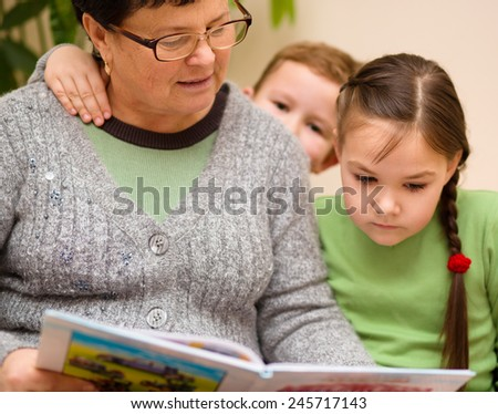 Grandmother is reading book with her grandchildren, indoors - stock photo
