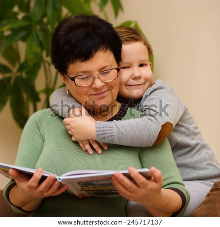 Grandmother is reading book with her grandson, indoor - stock photo