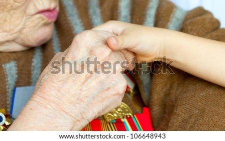 Grandmother kisses the hand of his grandson. Veteran of World War 2 - stock photo