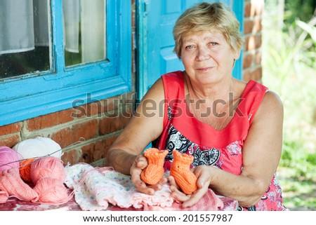 Grandmother knits for grandchildren - stock photo