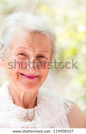 Grandmother looking at you confidently with her white hair and complimenting nice clothing. - stock photo