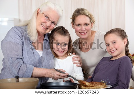 grandmother making crepes surrounded by daughter and grandchildren - stock photo
