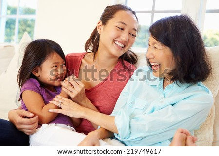 Grandmother Playing On Sofa With Granddaughter And Daughter - stock photo