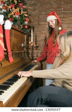 Grandmother playing the piano while her granddaughter (wearing a santa hat) looks on - stock photo