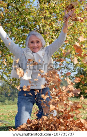 grandmother playing with a heap of dead leaves - stock photo
