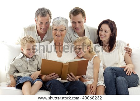 Grandmother reading a book to her family in living-room - stock photo