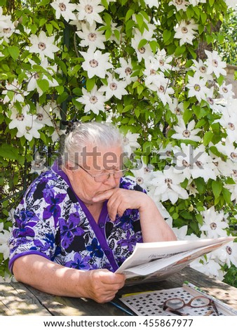 Grandmother reading a newspaper in the garden under a bush of flowers - stock photo