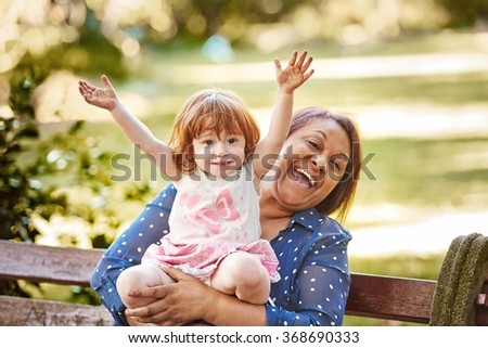 Grandmother sitting on a park bench with her granddaughter on her lap with her hands in the air - stock photo