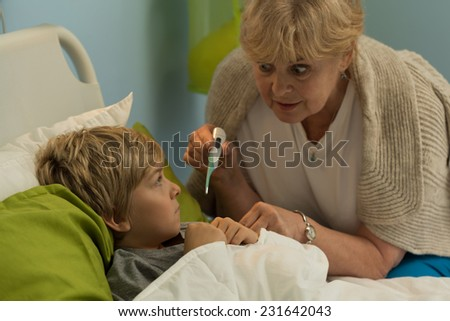 Grandmother taking temperature of his ill grandson - stock photo