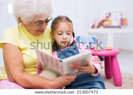 Grandmother teaches to read a book her granddaughter - stock photo